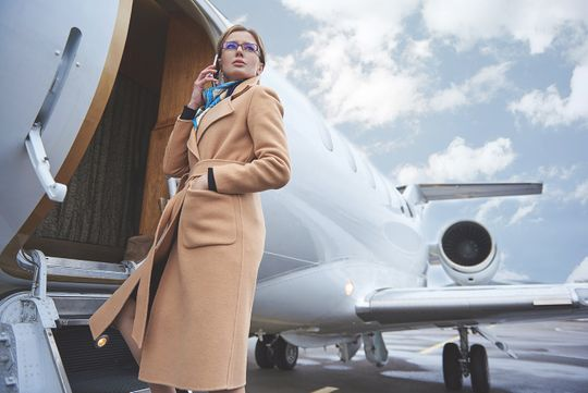 Woman boarding a private flight on her mobile